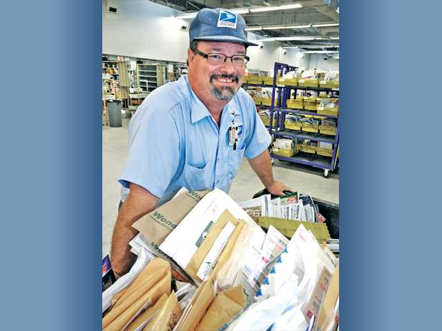 U.S. Post Office letter carrier Mike Andrews with his bin of mail ready for delivery at the Valencia branch of the U.S. Post Office. Signal photo by Dan Watson.