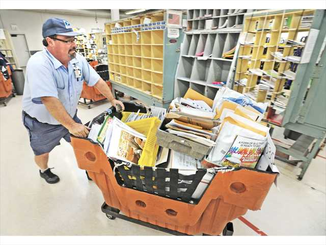 U.S. Post Office letter carrier Mike Andrews prepares to load his delivery vehicle at the Valencia branch of the U.S. Post Office on Thursday.