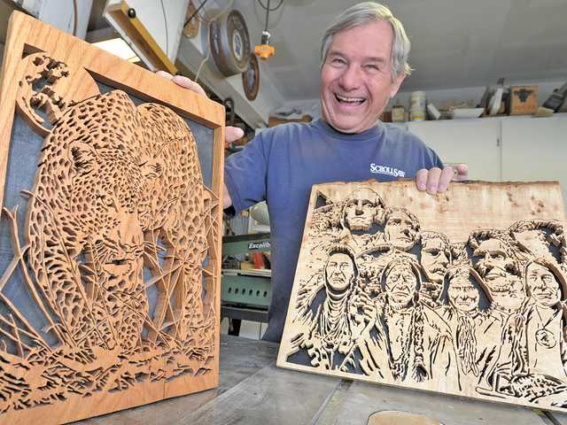 Scroll saw artist James McGuire, of Wood-N-Tole, displays two of his more intricate pieces of scroll saw artwork containing hundreds of individual cuts created in his garage in Canyon Country. Signal photo by Dan Watson.