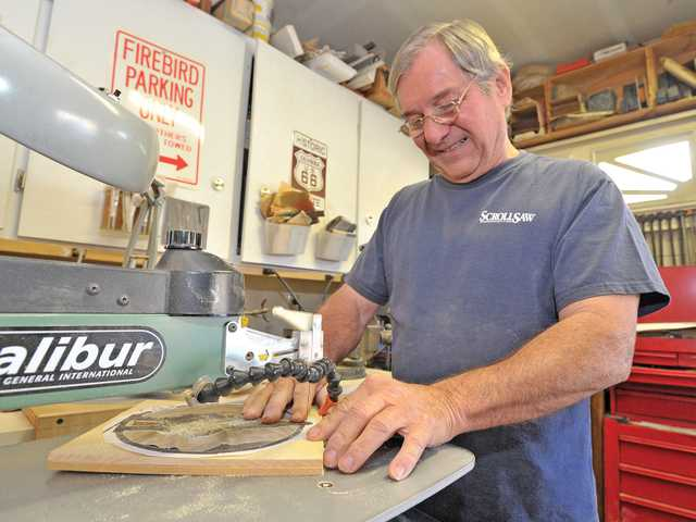 James McGuire, of Wood-N-Tole, cuts out a simple figure using his scroll saw in his garage workshop in Canyon Country.Signal photo by Dan Watson.