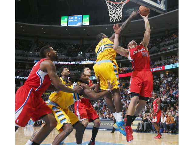 Clippers forward Blake Griffin, right, goes up for a shot as Denver Nuggets forward J.J. Hickson (7) covers on Monday in Denver.
