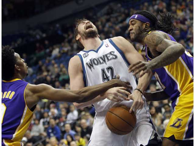 Minnesota's Kevin Love, center, is fouled by Los Angeles Lakers Nick Young, left, and Jordan Hill, right, on Tuesday in Minneapolis.