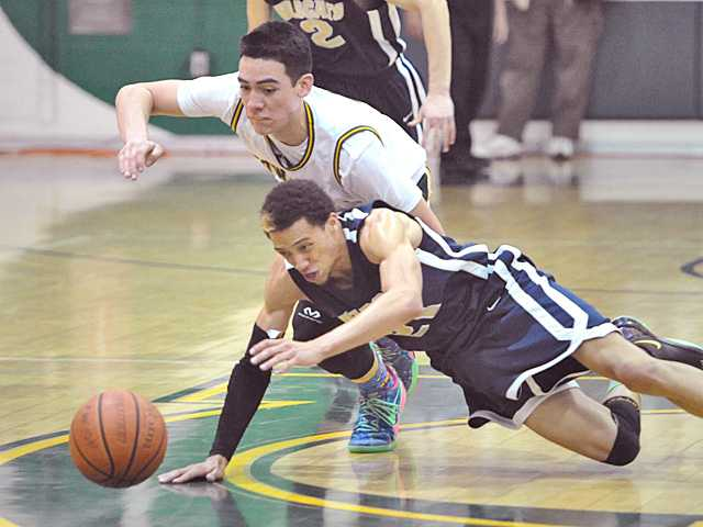 Christian Ware-Berry (21) recovers a loose ball against Canyon defender Ben Taufahema (3) at Canyon High on Tuesday.