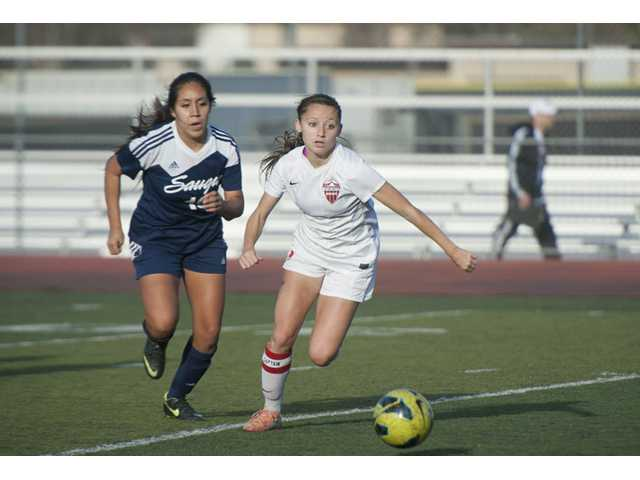 Hart's Sophia Cortes runs the ball down the field past Saugus's Yulissa Gonzalez at Hart High School on Tuesday.