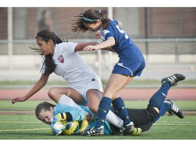 Hart's Destinney Duron, center, trips over Saugus goal keeper Maddie Hebert, bottom center, on Tuesday at Hart High.