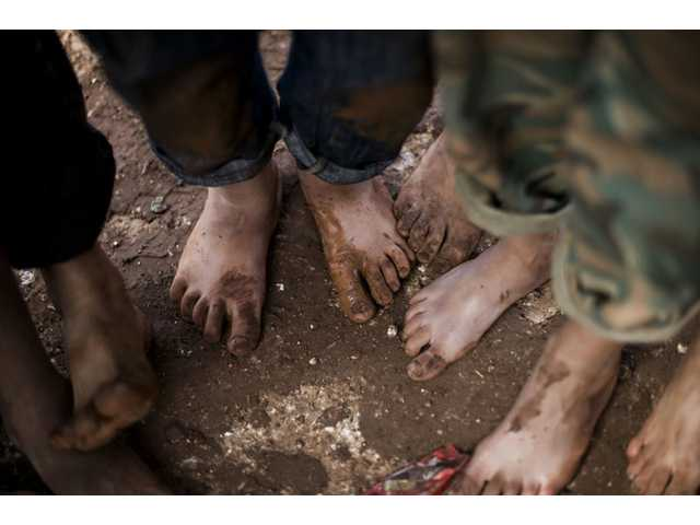In this file photo taken Oct. 26, 2012, displaced Syrian children gather barefoot in a refugee camp near Atma, Idlib province, Syria.