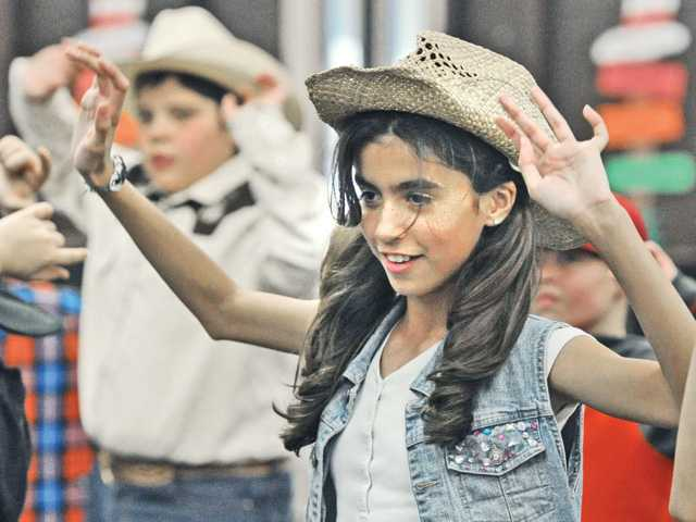 "Juliana Belnap, 10, dressed in a western hat and jeans, dances to the song ""Cotton-Eyed Joe"" with some her 60 fifth-grade classmates at the annual Western Hoedown fundraiser at Live Oak Elementary School in Castaic on Wednesday. Signal photo by Dan Watson."