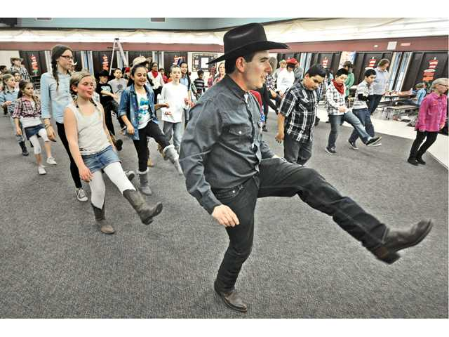 Castaic Physical Education teacher David Zieper, right, dressed in western clothes, dances with fifth-grade students at Live Oak Elementary School in Castaic on Wednesday during the fundrasier. Signal photo by Dan Watson.