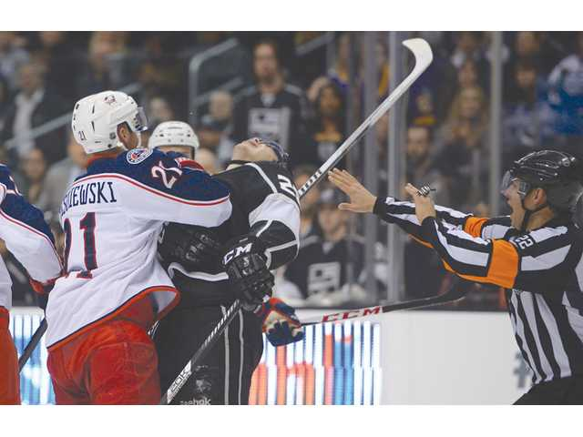 Columbus Blue Jackets defenseman James Wisniewski, left, hits Los Angeles Kings right wing Dustin Brown on Thursday in Los Angeles.