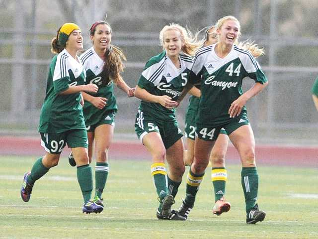 The Canyon girls soccer team celebrates following its first half goal against Valencia on Friday at Valencia High School.