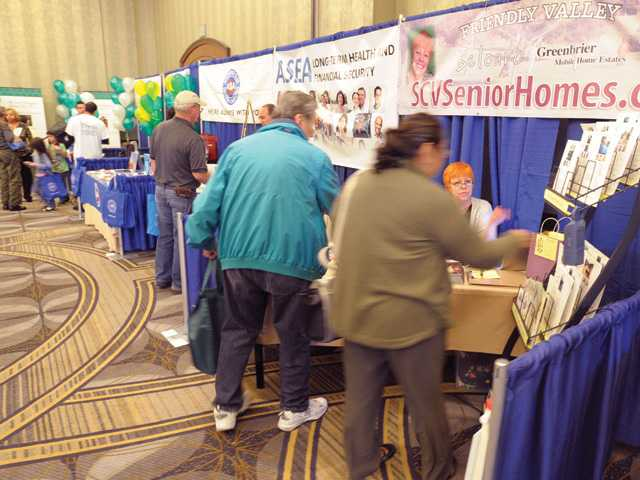 Attendees pick up informational materials from some of the 36 exhibitors at the Golden Years Expo and Senior Health Fair held at the Hyatt Regency Valencia on Saturday.