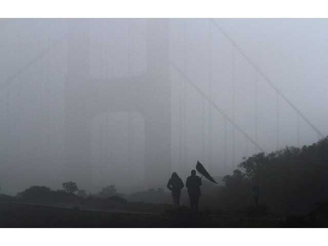 A gust of wind gets the better of an umbrella carried by a visitor overlooking the Golden Gate Bridge, in Sausalito, Calif. on Saturday.