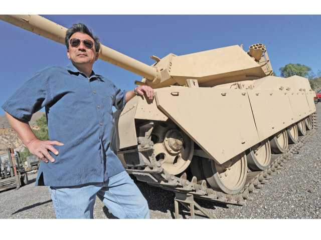 "David Wang, owner of Army Trucks Inc., stands next to a mocked-up British tank made to look like the latest U.S. Army M1 Abrams tank. Wang has rented out this tank from his Agua Dulce yard for movies such as ""Godzilla"" and ""Transformers."" Signal photo by Dan Watson."