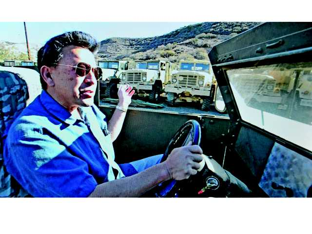 David Wang drives past rows of army trucks in desert camouflage at his Agua Dulce yard. Signal photo by Dan Watson.