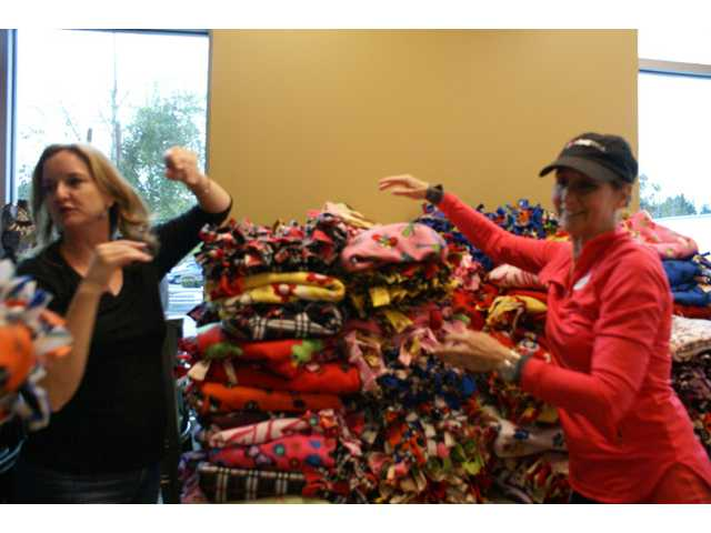 Blanket-making volunteers Mary K. Judy, left, and Sue Tweddell stack the scores of blankets made Sunday for the group Mending Kids International at NorthPark Community Church. Photo by Jim Holt.