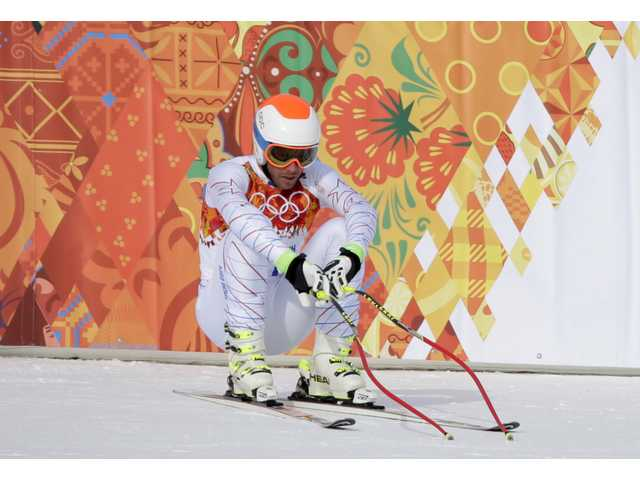 America's Bode Miller sits on his skis after finishing the men's downhill at the Sochi 2014 Winter Olympics on Sunday.
