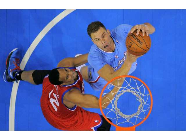 Los Angeles Clippers forward Blake Griffin, right, puts up a shot as Philadelphia 76ers forward Evan Turner defends on Sunday in Los Angeles.
