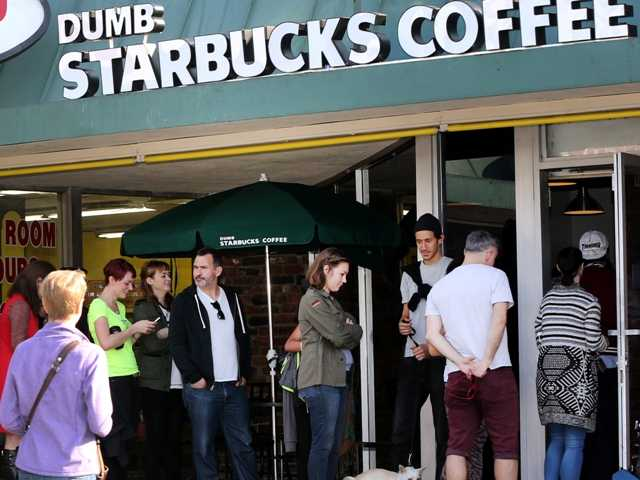 People line up at Dumb Starbucks coffee in L.A. The store resembles a Starbucks with a green awning and mermaid logo, but a Starbucks spokesperson said the store is not affiliated with Starbucks.
