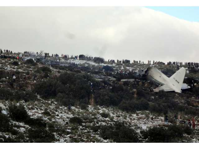 People look at the wreckage of Algerian military transport plane after it slammed into a mountain in the country's rugged eastern region on Tuesday.