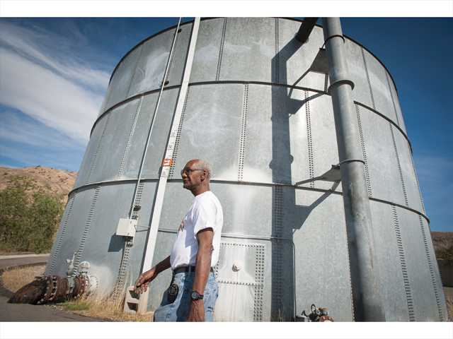 Charles Sturkey, director of operations for LARC Ranch, walks past the 300,000- gallon water tank at the ranch in Bouquet Canyon on Wednesday. Signal photo by Charlie Kaijo.