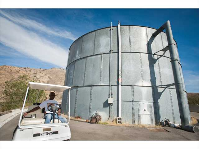 Charles Sturkey, director of operations for LARC Ranch, sits in a golf cart next to the 300,000- gallon water tank at the ranch in Bouquet Canyon on Wednesday. Signal photo by Charlie Kaijo.