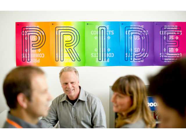 Workers from Facebook's health center gather near a banner promoting gay pride at the company's Menlo Park headquarters Wednesday.