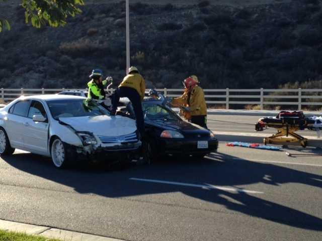 Firefighters work to free the occupant of one of the cars involved in a collision in Valencia today. Two were taken to the hospital from the scene. Photo courtesy of Gail Pinsker
