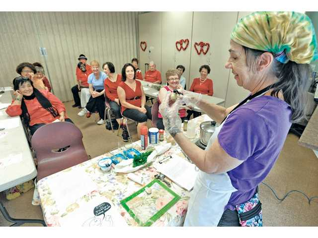Registered Dietitian Stephanie Correnti, right, shaves a piece of ginger root using a potato peeler as she prepares a healthy curry chicken recipe for a class on nutrition to a group 19 seniors at the SCV Senior Center on Friday.