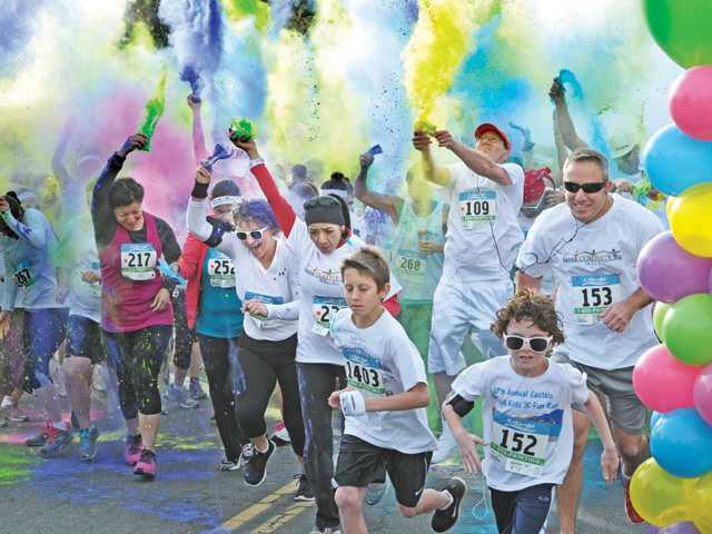 Runners take off under a cloud of colored corn starch at the start of the first of three 5K fun runs at the Santa Colorita Run event held at Castaic Lake on Saturday.