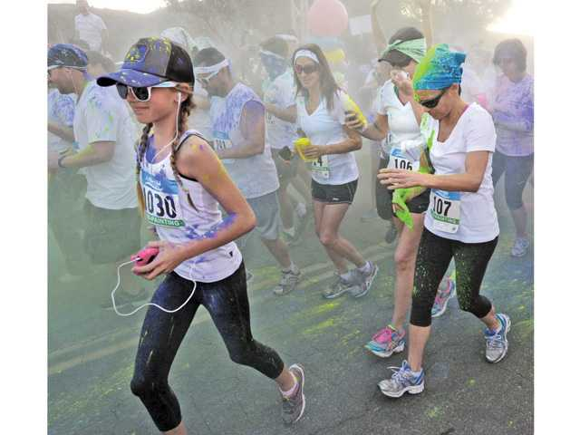 Hundreds of runners covered with colored corn starch leave the starting line of the first of three 5K fun-runs at the Santa Colorita Run event held at Castaic Lake on Saturday.