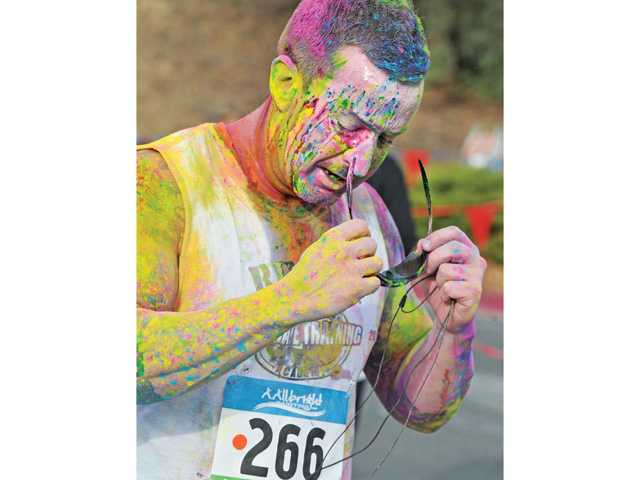 Runner Dave Cirricione crosses the finish line covered with colored corn starch ahead of hundreds of runners to finish fourth in the first of three 5K fun-runs at the Santa Colorita Run event.