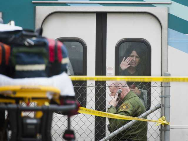 A Metrolink passenger tries to get the attention of a sheriff's deputy following a train collision with a man on the tracks Tuesday near the Newhall Metrolink station. Signal photo by Charlie Kaijo