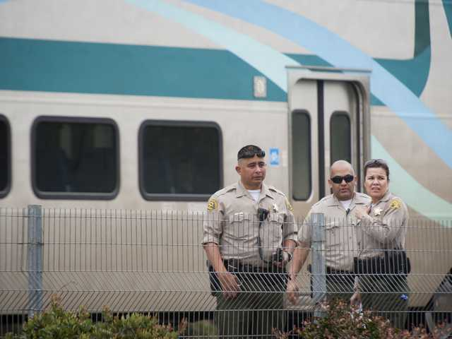 Sheriff's deputies stand by the scene where a man was hit by a Metrolink train on Tuesday. Signal photo by Charlie Kaijo