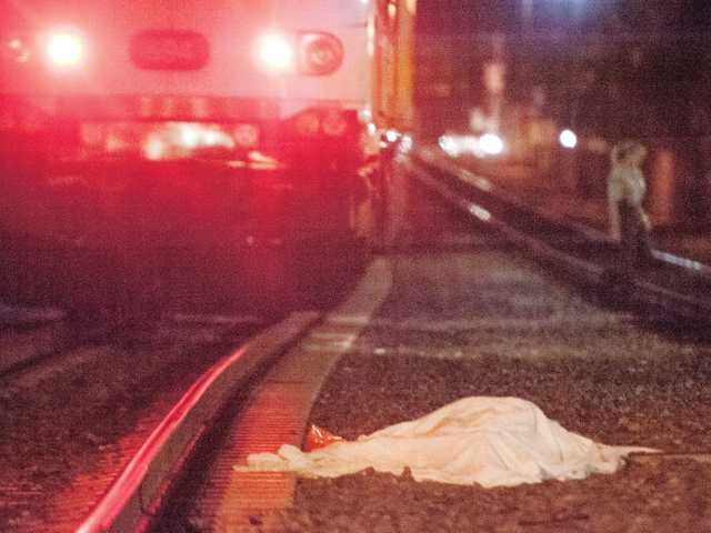 A covered body lays on the track at the Metrolink station in Newhall after the victim reportedly stepped in front of an oncoming train Tuesday. Signal photo by Charlie Kaijo