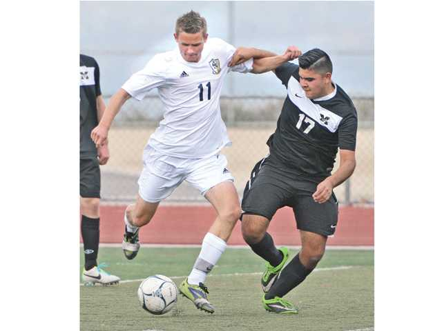 West Ranch's Derek Milleman (11) fights for the ball with Bishop Montgomery High School's Mark Falcon (17) at West Ranch High on Tuesday.