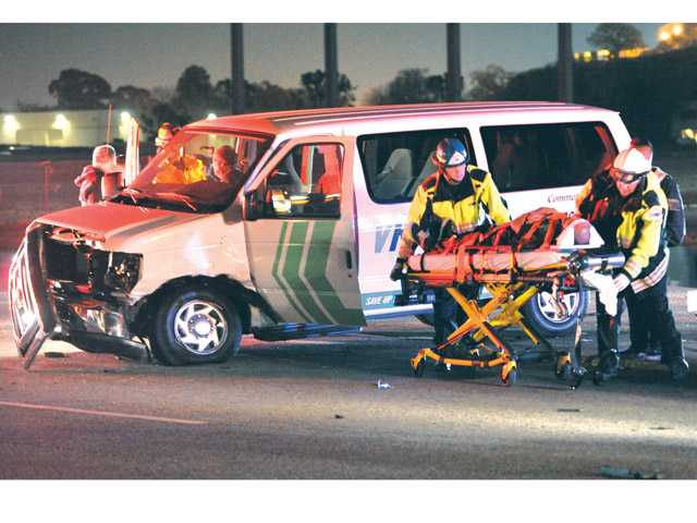 Firefighters remove one of several occupants of a carpool van that collided with a black sedan on Rye Canyon Road near Avenue Crocker in Valencia on Tuesday evening. Signal photo by Dan Watson.