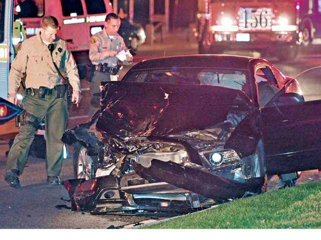 SCV sheriff's deputies prepare a black sedan for transport by tow truck after it collided with a carpool van containing several occupants in Valencia on Tuesday evening.Signal photo by Dan Watson.