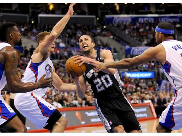 San Antonio Spurs guard Manu Ginobili (20) drives past Los Angeles Clippers defenders on Tuesday in Los Angeles.