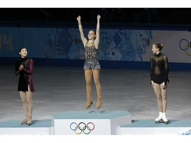 Adelina Sotnikova of Russia, centre, Yuna Kim of South Korea, left, and Carolina Kostner of Italy stand on the podium during the flower ceremony for the women's free skate figure skating final at the 2014 Winter Olympics on Thursday in Sochi, Russia.