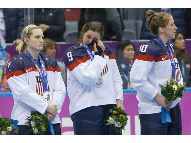 Megan Bozek, center, of the United States wipes a tear as she stand with teammates Monique Lamoureux, left, and Meghan Duggan during the medal ceremony for the women's ice hockey tournament at the 2014 Winter Olympics on Friday in Sochi, Russia.