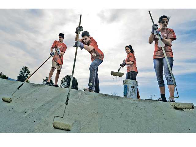 Trinity Classical Academy ninth-graders, from left, Sumner Howell, Caden Kulp, Alycia Garcia and Ryann Campuzano paint the side of a retaining wall in Canyon Country on Thursday. Signal photo by Dan Watson.