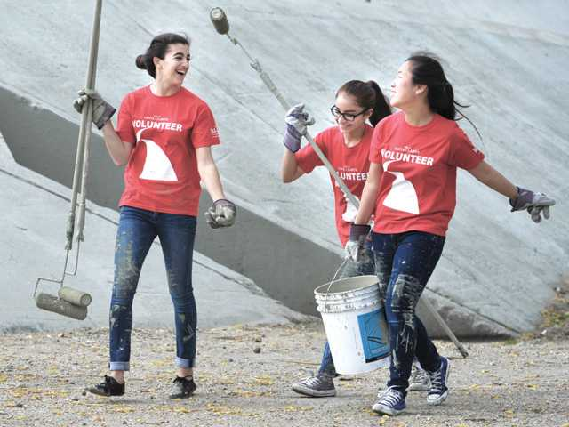 Trinity Classical Academy ninth-graders,  from left, Sarah Howell, Caitie Galan and Jenny Chang move to a new location as they paint the side of the wall. Signal photo by Dan Watson.