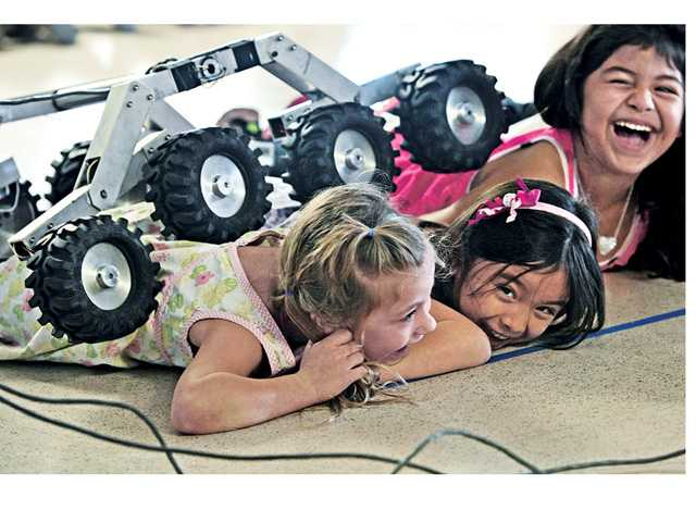 "Santa Clarita Elementary School kindergarteners, from left, Violet Abadi, Liberty French and Lizelle Gonzalez react as ""Sammy"" the NASA Mars rover model crawls over their backs during a science assembly presented by the Jet Propulsion Laboratory for the school in Saugus on Thursday. Signal photo by Dan Watson"