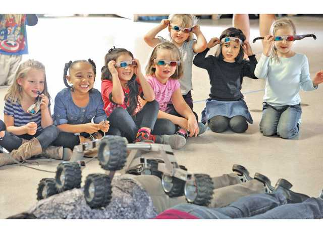 "Santa Clarita Elementary School first-graders look on as a NASA Lead Resources Analyst Dennis Young, left, demonstrates the climbing ability of ""Sammy,"" a NASA Mars rover model presented to the Saugus school kids Thursday. Signal photo by Dan Watson"