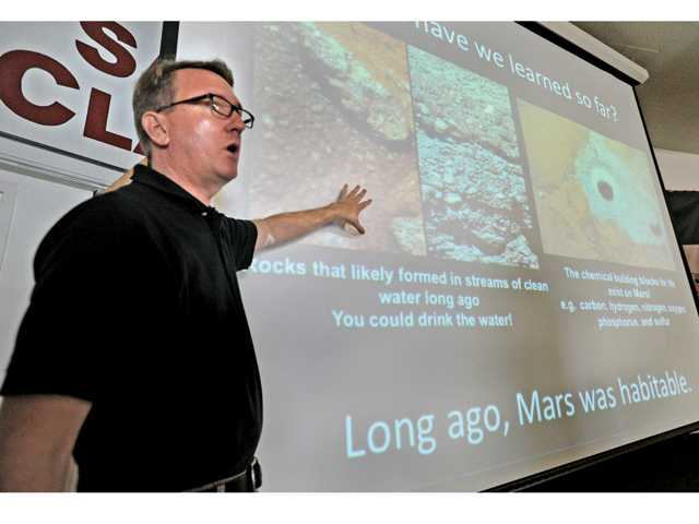NASA Lead Resources Analyst Dennis Young shows a slide of what scientists think were the effects of running water on Mars during a science assembly presented at Santa Clarita Elementary School on Thursday. Signal photo by Dan Watson