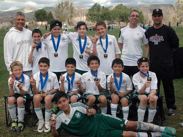 "Coach Dan Sanchez, left, back row, and on the right back row, Assistant Coaches Stephen De Vita and Albert Garcia, with the area 10S Champions Canyon Country BU12 ""Extra.""   Bea Johnston/courtesy photo"