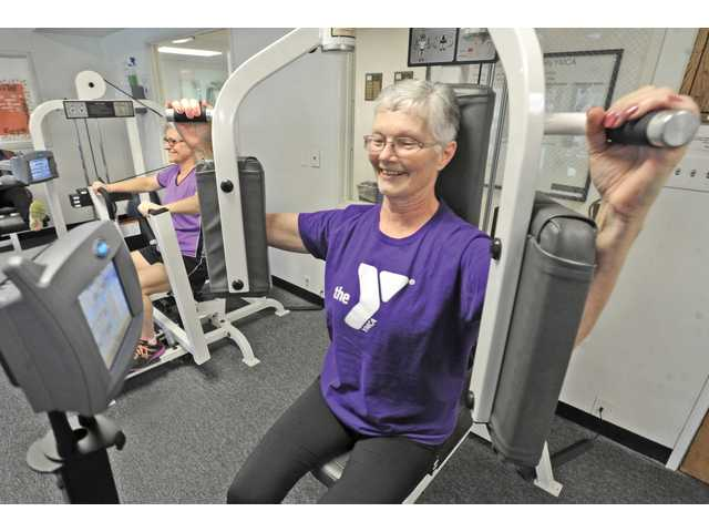 Jeanie Smith, right, does pectoral fly exercise and Denise Grimes, rear, does chest press.