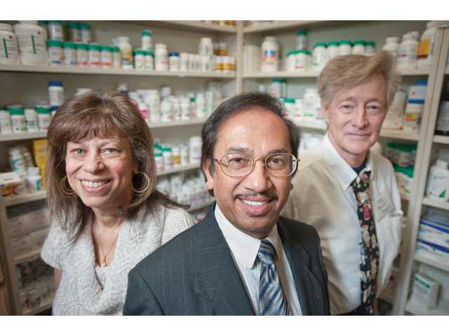Moazzem H. Chowdhury poses with pharmacy tech, Debra Stratford, and pharmacist, Bill Henderson, at Desert Drug Pharmacy.