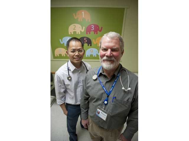Dr. Tim Do and Dr. Thomas Connolly stand for a portrait in an examination room at the Facey Medical Group building in Saugus.
