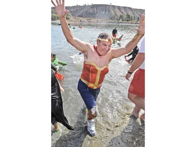 Castaic Lions Club Lion Tamer Bill Kimble wears a Wonder Woman costume as he exits the chilly water of the lower lake of Castaic Lake for the 2014 Polar Plunge Spcial Olympics fundraiser on Saturday.